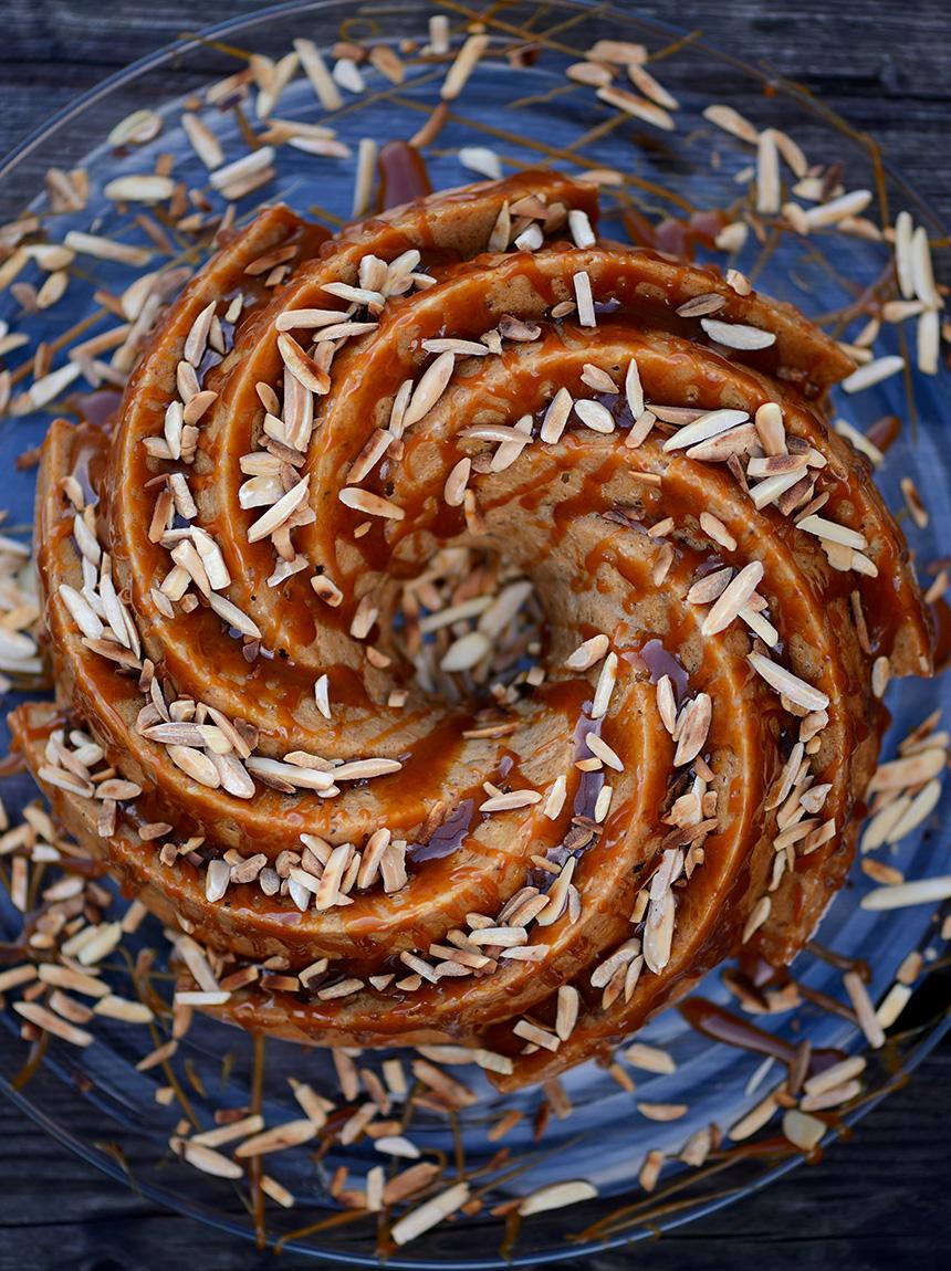 Der jüdische Apfelkranz wird in einer spiralförmigen Gugelhupfform gebacken, anschließend mit einer Honig-Toffee-Glasur beträufelt un dann mit gerösteten Mandelsplittern bestreut.