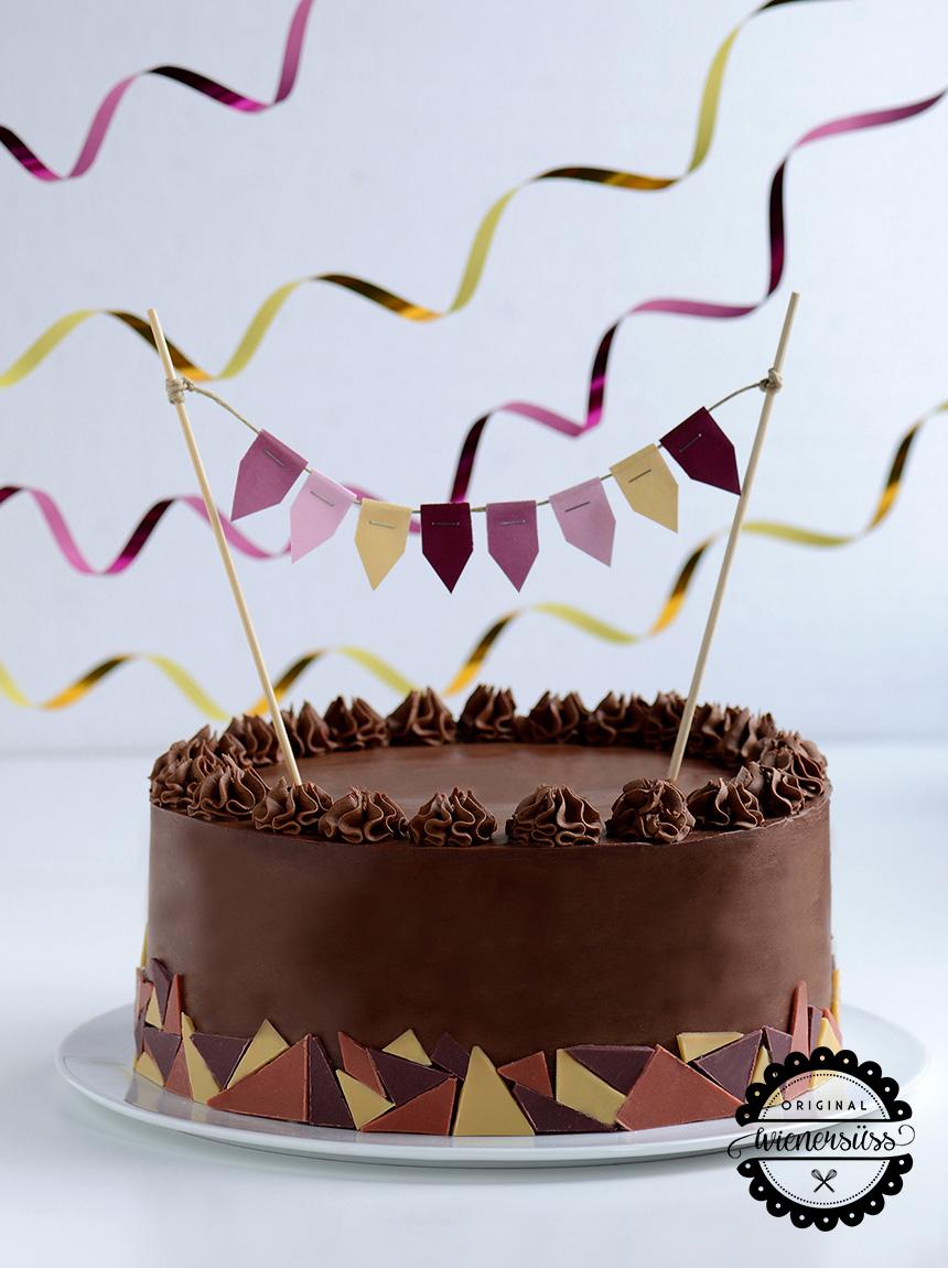 Die Brownietorte ist mit Schokolade überzogen und mit einem Mosaik aus rosa, roten und gelben Schokodreiecken dekoriert. Farblich passend steckt eine Wimpelgirlande in der Torte.