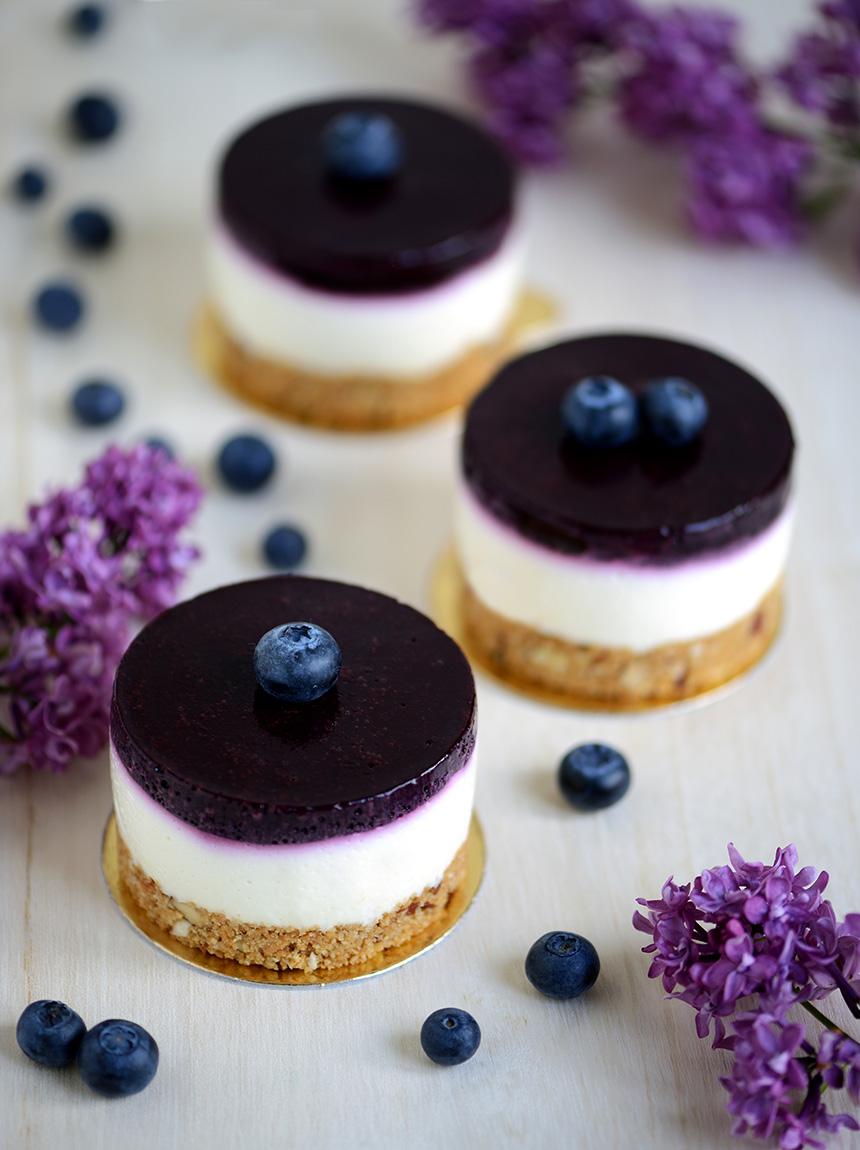 Die kleinen Blueberry Cheesecake Törtchen beeindrucken mit brillanten Farben - dunkles lila in der Heidelbeerschicht, strahlendes weiß die Cheesecakemasse und sattes Hellbraun der Knusperkeksboden.